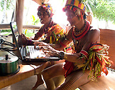 INDONESIA, Mentawai Islands, Kandui Resort,  tribal senior tribal man pretending to use a laptop
