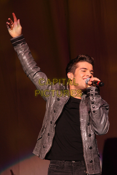 JOE McELDERRY.BRMB Live 2010 at the LG Arena, Birmingham, England..November 27th 2010.half length stage concert live gig performance music singing black grey gray jacket leather jeans denim arm in air.CAP/JIL.©Jill Mayhew/Capital Pictures