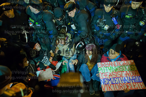 Protesters sit in front of a line of riot police during a demonstration against government corruption in Budapest, Hungary on December 16, 2014. ATTILA VOLGYI