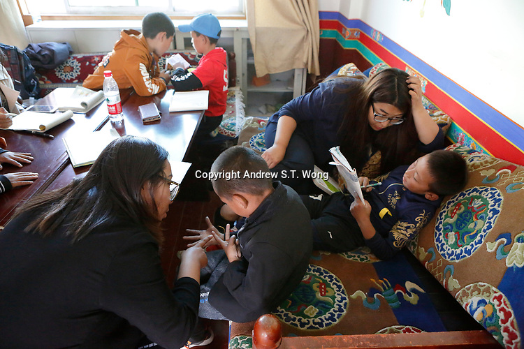 Lhasa, Tibet, China - Tibetan educator Deqingyuzhen (R) teaches a young student to read during free classes at a community centre in Lhasa, September 2018.