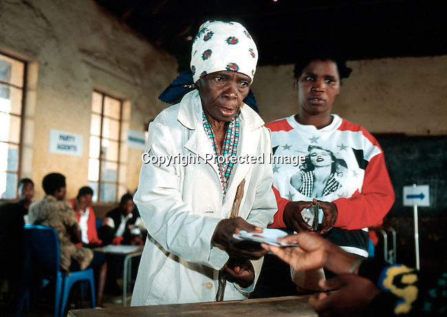 poelec990043 Politics. Elections. A voting line in Kwa Mashu, a township outside Durban, South Africa. An elderly woman is helped to the voting both. People voted on June 2nd, 1999, the second democratic election in the new South Africa..Photo: Per-Anders Pettersson/iAfrika Photos
