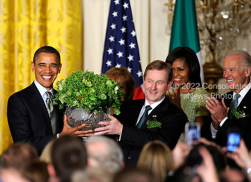 United States President Barack Obama (L) accepts a bowl of shamrocks from Irish Prime Minister Enda Kenny as first lady Michelle Obama (2nd,R) and Vice President Joe Biden (R) during a reception in the East Room of the White House, March 20, 2012, in Washington, DC. The two leaders concluded a working day devoted to discussions on economic matters, Ireland's peace keeping participations and foreign policy issues like Syria and Iran.   .Credit: Mike Theiler / Pool via CNP