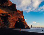 The massive basalt columns tower over the splendid Reynisfjara black sand beach next to H&aacute;lsanefshellir Cave near the southern town of V&iacute;k. While the wandering tourist cloaked in red made for a fine image, we would strongly recommend against approaching the edge of the ocean as she did. The sheer power of the roar of the crashing surf draws forth an evolutionary impulse fear in the pit of your stomach. That fear is justified as rogue waves can drag the unwitting out to sea in an instant. Signs and caution tape warn, but are continually crossed. This image was shot on auto at 1/350th of a second on 50 iso. <br /> <br /> Photo: Brinson+Banks