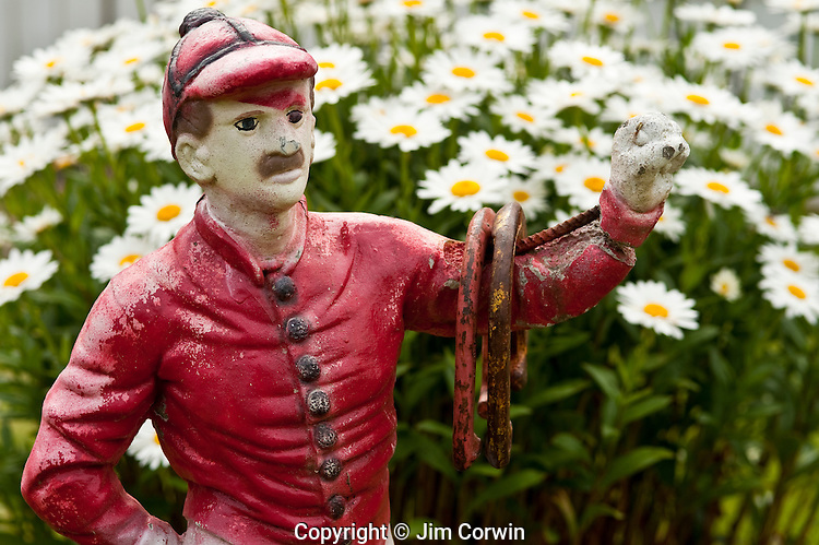 Metal sculpture jockey holding horseshoes in his arms