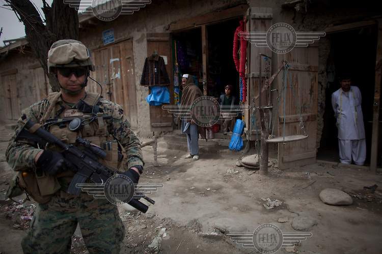 Marines patrol in Nishigham village close to the Pakistan border in Nuristan. The day's mission was to re-supply an OP (Observation Post) that had been attacked the day before killing one ANA (Afghan National Army) soldier. The marines are acting as an ETT (Embedded Training Team) to mentor the ANA with the ultimate aim of leaving the country's security for the local Army to deal with.