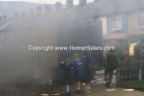 Northern Ireland The Troubles. 1980s. School children walk past a burnt out hijacked lorry, British soldier investigates.