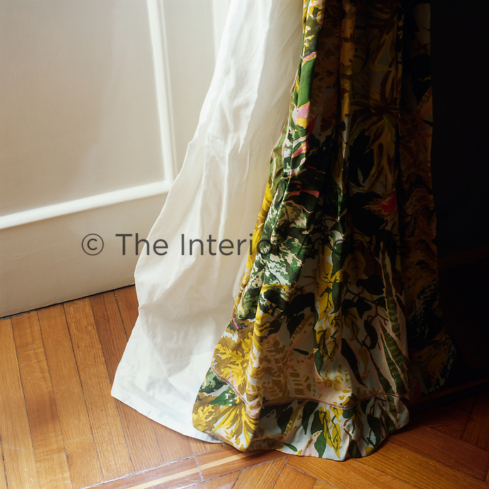 A curtain in a green and yellow floral pattern fabric drapes onto the parquet floor.