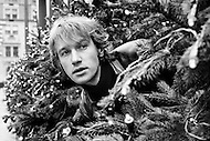 December 1969 --- French actor Yves Renier peeks out from between to Christmas trees on a New York street. --- Image by © JP Laffont