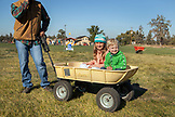 USA, Oregon, Bend, young kids play around in a wheelbarrow during the annual pumpkin patch located in Terrebone near Smith Rock State Park