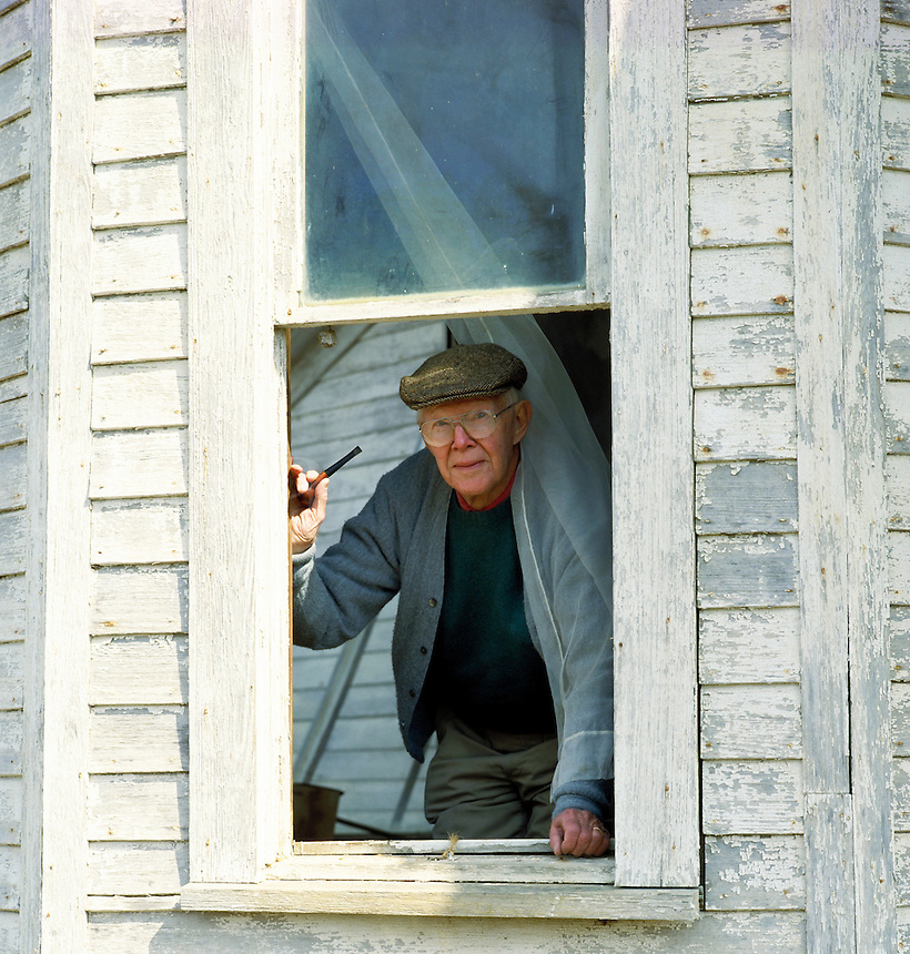Man looks out from window of an old house in the country. Tom Harding. Arkansas.