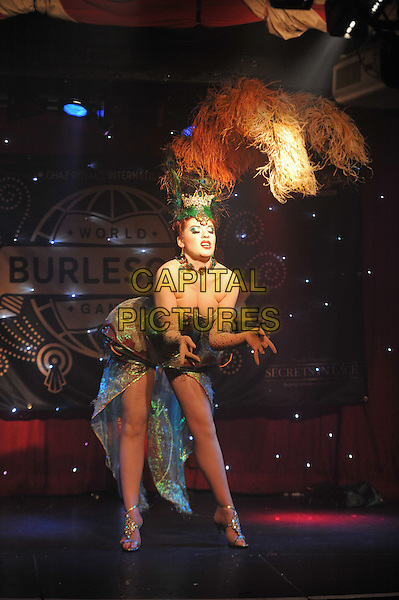 World Burlesque Games Closing Night held at Madam JoJo's, Soho, London, England. .13th May 2012.on stage performance performing full length bending leaning cleavage orange yellow green  feathers hat .CAP/MAR.© Martin Harris/Capital Pictures.