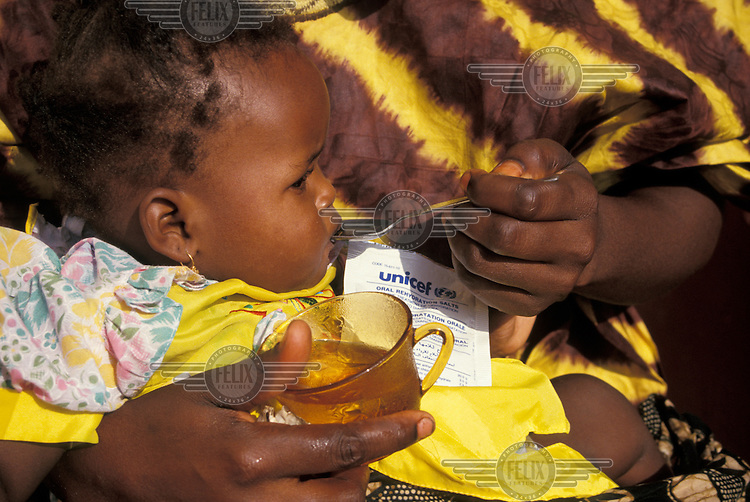 Young child receiving oral rehydration salts at health clinic.