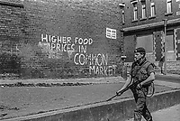 British soldier on peace-keeping duty in West Belfast passing anti-EU grafitti in the run-up to the 5th June 1975 United Kingdom European Community (Common Market) membership referendum. 197505250466<br />