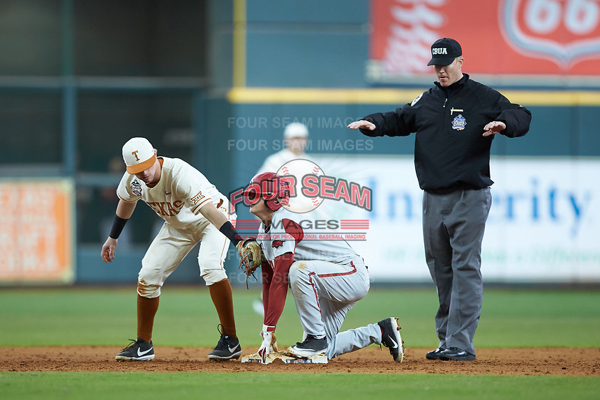 Second base umpire Seth Buckminster makes a safe call as Brenden Dixon (1) of the Texas Longhorns applies a tag to Jacob Nesbit (5) of the Arkansas Razorbacks during game six of the 2020 Shriners Hospitals for Children College Classic at Minute Maid Park on February 28, 2020 in Houston, Texas. The Longhorns defeated the Razorbacks 8-7. (Brian Westerholt/Four Seam Images)