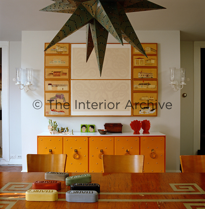 Paintings by Riley Andersen hang above a sideboard by Tommi Parzinger in the dining room