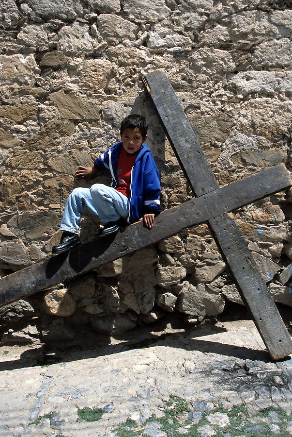 A boy sits on a cross, Real de Catorce, Mexico.