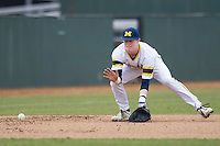 Michigan Wolverines third baseman Jacob Cronenworth (2) fields a ground ball during the NCAA baseball game against the Washington Huskies on February 16, 2014 at Bobcat Ballpark in San Marcos, Texas. The game went eight innings, before travel curfew ended the contest in a 7-7 tie. (Andrew Woolley/Four Seam Images)