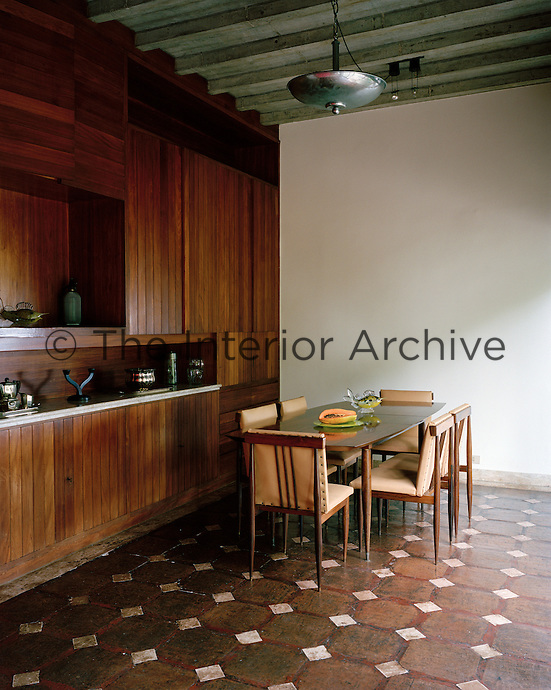 The dining room contrasts a concrete ceiling with a terracotta tiled floor and a wall of built-in wooden cupboards