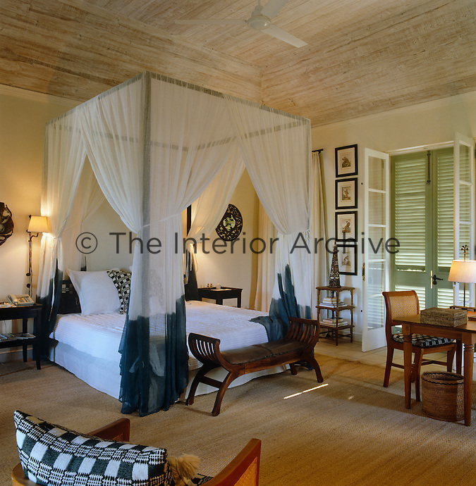 The hangings on the four-poster bed in this guest bedroom are of Indian voile which has been hand-dyed at the ends