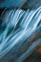 The image of a small waterfall as water is  flowing energetically over rocks at the Grand Teton National Park in Wyoming.