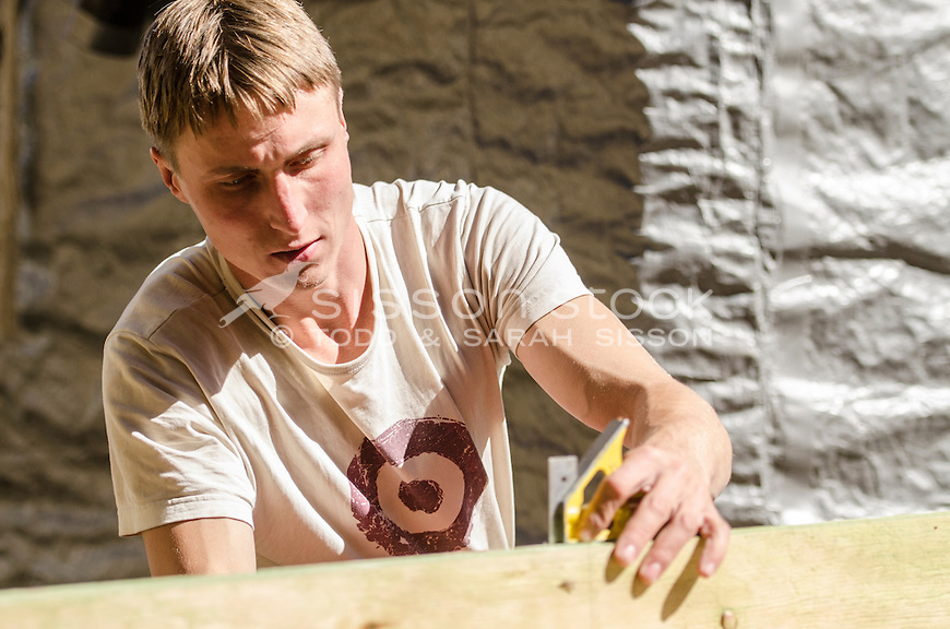Builder | Carpenter using set square to  mark wood on a construction site, New Zeaalnd - stock photo, canvas, fine art print