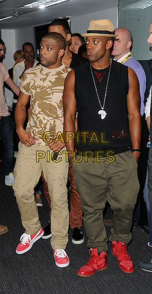 "JLS - JONATHAN ""JB"" GILL & ORITSE WILLIAMS.The Capital FM Summertime Ball, Wembley Stadium, London, England..June 12th, 2011.full length beige khaki trousers studs studded sleeveless black top print t-shirt hat hands in pockets african necklace silver .CAP/CAN.©Can Nguyen/Capital Pictures."