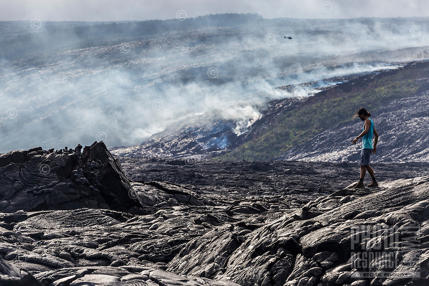 A woman hikes through lava fields to get a better view of new lava flow, Hawai'i Volcanoes National Park, Hawai'i Island.