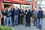 12/11/2013 – Farewell and cheers! Regulars at Ollie's Bar, James Street, raise their hats and their glasses in farewell as the hearse bearing the coffin of their late friend Paddy Cluskey halted briefly outside his favourite pub.