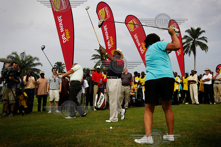 Obong Victor Attah (centre), the governor Akwa Ibom state, hits a ceremonial first ball with professional golfers American Nancy Lopez (right) and Scottish Colin Montgomerie (left) at the opening of a new golf course.