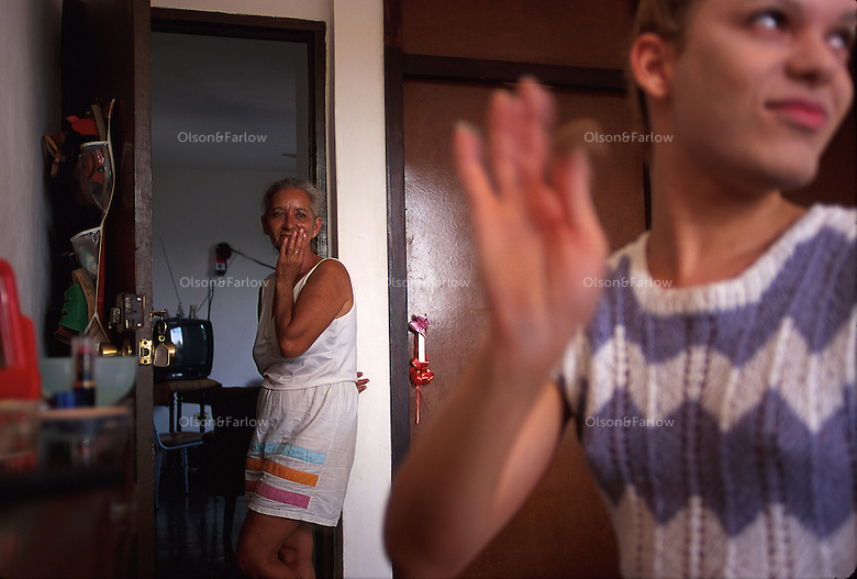 While Alexander puts on makeup to go out to a club, her mother, Ligia, watches from the bedroom doorway. Mother and son are very close and make their home together. His mother cooks, washes the clothes and keeps house since her health problems have recently kept her from work. Alexander is comfortable with her life as a transvestite. She was issued an identification card by the government as a woman