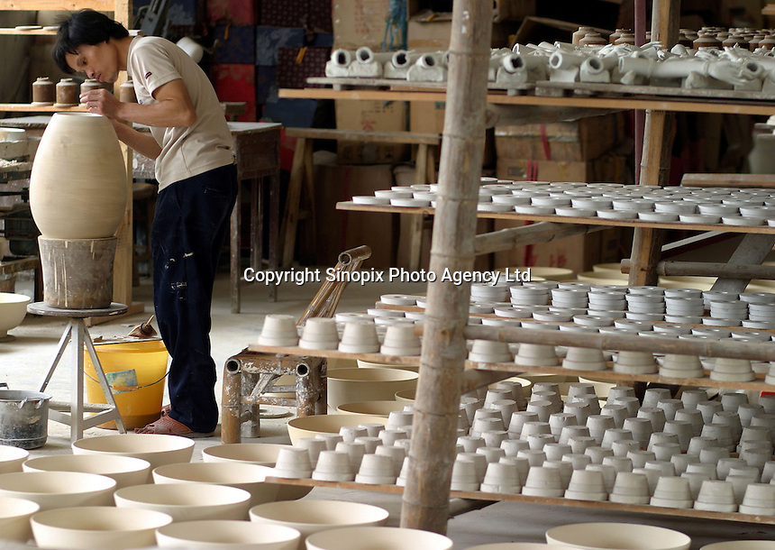 A Chinese worker makes puts the finishing touch onto a clay vase at a porcelain workshop in Jingdezhen, Jiangxi Province, China. The township of Jingdezhen is well known in China as the country's porcelain capital ever since it was selected exactly one thousand years ago as the royal porcelain provider for the imperial court..24-JUN-04