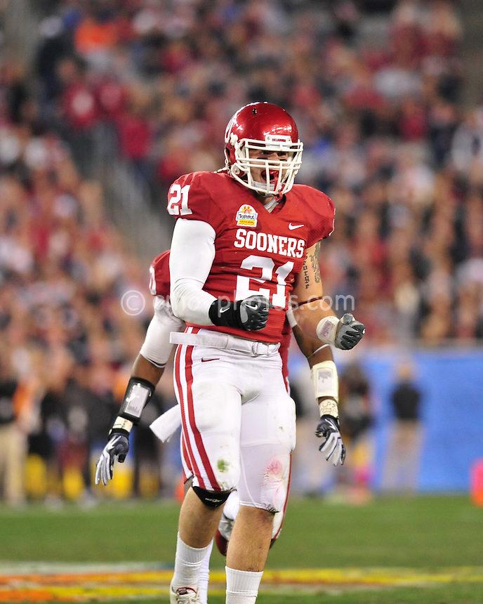 Jan 1, 2011; Glendale, AZ, USA; Oklahoma Sooners linebacker Tom Wort (21) reacts to a third-down stop in the 3rd quarter of the 2011 Fiesta Bowl against the Connecticut Huskies at University of Phoenix Stadium.  The Sooners won the game 48-20.