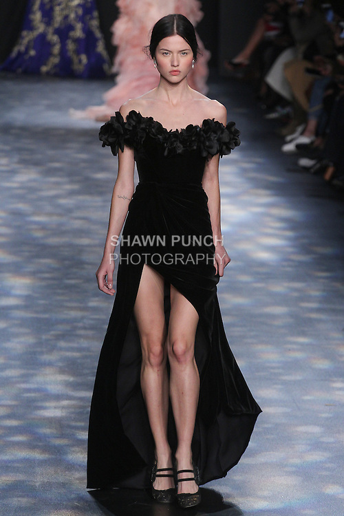 Model Isis walks runway in a black velvet off-the-shoulder column gown with high slit embellished with laser-cut organza and velvet flowers, from the Marchesa Fall 2016 collection by Georgina Chapman and Keren Craig, presented at NYFW: The Shows Fall 2016, during New York Fashion Week Fall 2016.