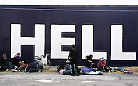 Pictured: Migrants rest on the ground next to a ship Tuesday 01 March 2016<br /> Re: Migrants at the port of Piraeus, near Athens, Greece