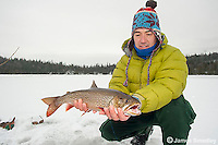Angler holding up a splake caught ice fishing.