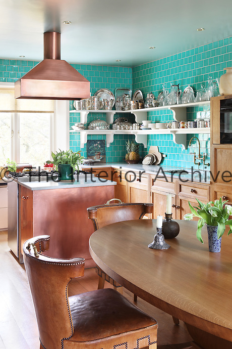 Striking turquoise ceramic tiles line the walls of the kitchen forming a backdrop to the oak units and copper hood