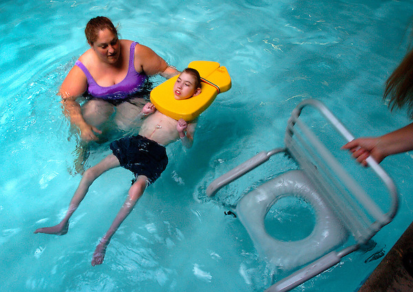 Roosevelt Middle School student Jacob Riebau floats in the pool as Assistant Aid Nikki Wilkins watches.  Jacob is wheeled into the water on a wheelchair access ramp. Jacob is so comforable in the water on this day he almost falls asleep in the warm waters of the Mary Lou Clack therapy pool.