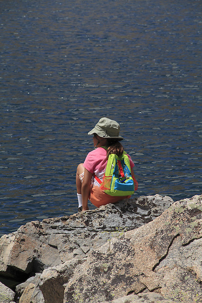 Girl sitting at a lake, west of Boulder, Colorado, USA. .  John leads private photo tours throughout Colorado. Year-round Colorado photo tours.