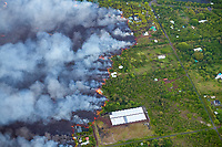 lava originating from Kilauea Volcano, erupting from fissure 8 in Leilani Estates, near the town of Pahoa, flows through Kapoho, destroying agricultural properties and burning crops, shade houses, dwellings, other structures, and streets, Puna, Big Island, Hawaii, USA