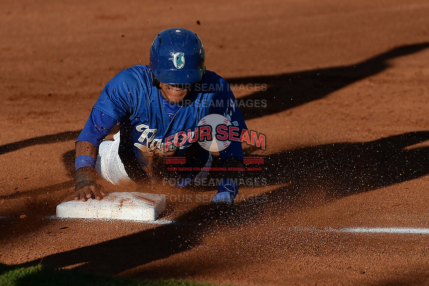 Jesmuel Valentin (6) of the Ogden Raptors slides head first into third base in action against the Great Falls Voyagers at Lindquist Field on August 13, 2013 in Ogden Utah. (Stephen Smith/Four Seam Images)
