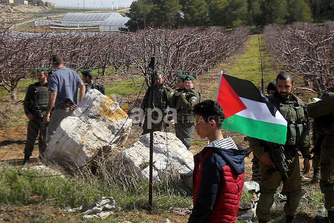 Palestinian protesters holds a national flag during a demonstration against the construction of Jewish settlements in the occupied West Bank city of Hebron, on February 10, 2017. Photo by Wisam Hashlamoun