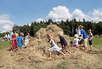 Leusden -  De Stichting Behoud Oude Werktuigen organiseert de jaarlijkse oogstdag op landgoed Den Treek. Kinderen , waarvan enkelen in boeren klederdracht, spelen in het hooi