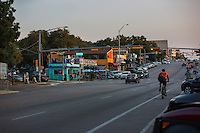 A bicycle rider rides up South Congress Avenue, a popular hip neighborhood featuring eclectic shops, restaurants and live music venues - Stock Image.