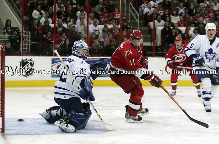Carolina's Justin Williams (11) gets a shot past Toronto goalie Mikael Tellqvist (32), but it goes just wide of the net on Friday, November 25, 2005, at the RBC Center in Raleigh, North Carolina during a regular season NHL game. Carolina Hurricanes defeated the Toronto Maple Leafs 4-3 on the strength of a 2-0 shootout victory after overtime.
