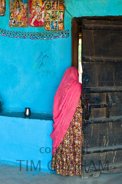Hindu woman in traditional blue painted home in Hindu Brahman high caste village of Dhudaly  in Rajasthan, Northern India
