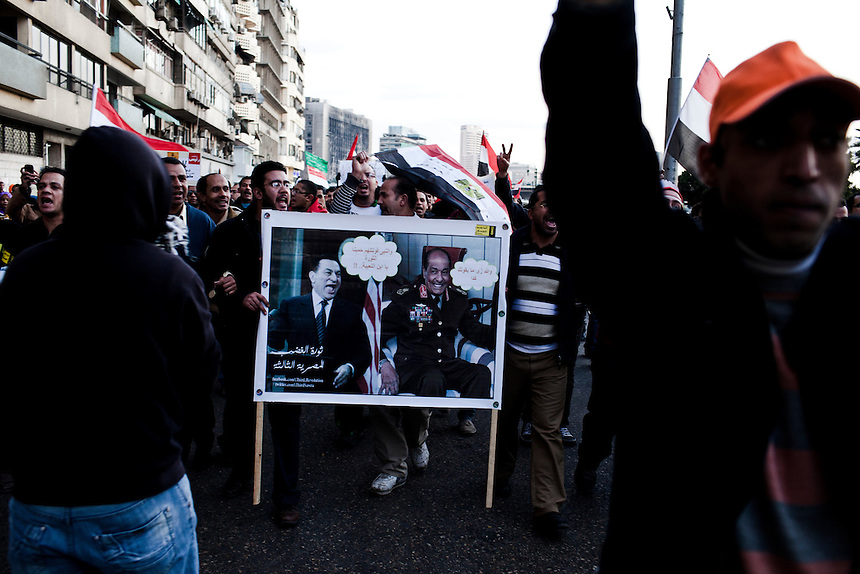 A crowd of proteters holds a banner showing former President Hosni Mubarak and Field Marshall Tantawi while en route toward the 'Maspero' Ministry of Information building, Cairo, January 25, 2012. Protsters marked the first anniversary of the Egyptian revolution by packing into the city's infamous Tahrir Square. An overflow of protesters moved on to the Maspero building that afternoon. Photo: Ed Giles.