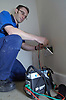 Housing Association electrician testing electrical circuit in an empty property; NE England UK