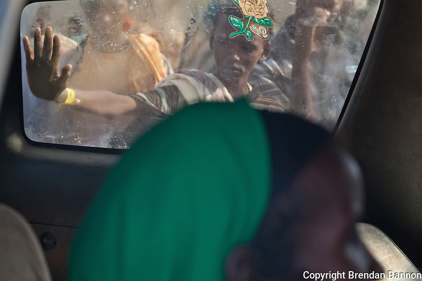 A refugee woman witha sick child inside of an MSF ambulance and the crowd that gathered outside. Dadaab refugee camp, Kenya.