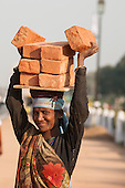 Delhi, India. Woman worker carrying eight bricks on her head, smiling.
