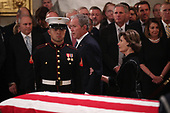 Former President George W. Bush walks past his father's casket with his wife former first lady Laura Bush during services for former President George H.W. Bush in the U.S. Capitol Rotunda in Washington, U.S., December 3, 2018. REUTERS/Jonathan Ernst/Pool